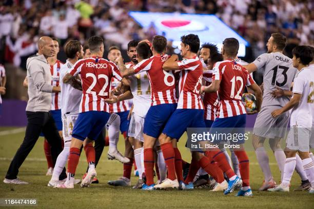 Head Coach Zinedine Zidane of Real Madrid tries to help players from Atletico de Madrid and Real Madrid try to stop Daniel Carvajal of Real Madrid...