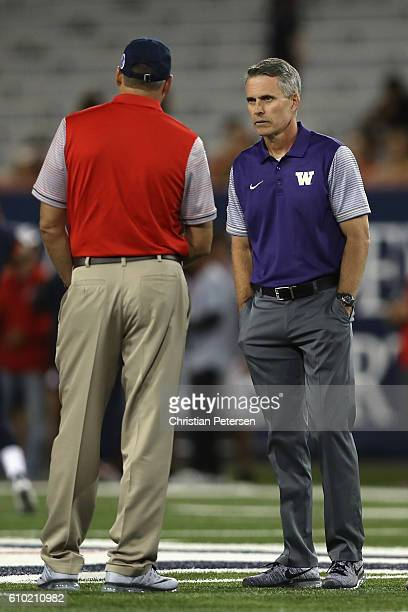 Head coaches Chris Petersen of the Washington Huskies and Rich Rodriguez of the Arizona Wildcats talk during warm ups to the college football game...