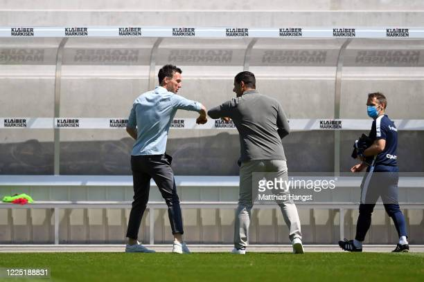 Head coaches Christian Eichner of Karlsruhe and Dimitrios Grammozis of Darmstadt do an elbow bump prior to the Second Bundesliga match between...