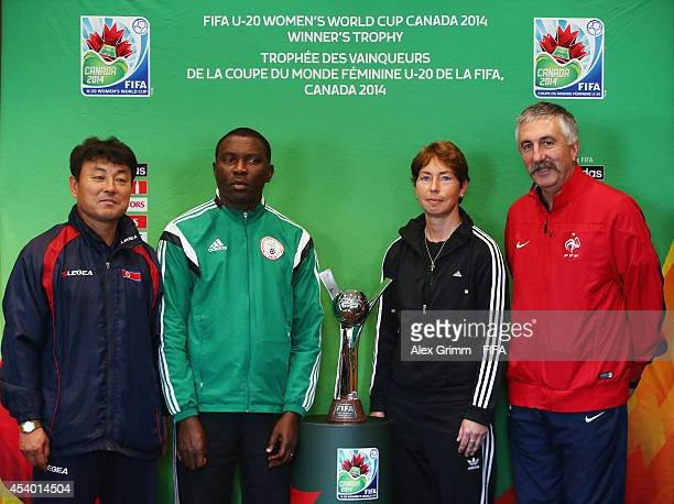 Head coaches Hwang Yong Bong of Korea DPR Peter Dedevbo of Nigeria Maren Meinert of Germany and Gilles Eyquem of France pose with the trophy during...