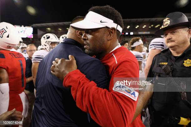 Head coaches Kevin Sumlin of the Arizona Wildcats and Kalani Sitake of the Brigham Young Cougars shake hands following the college football game at...