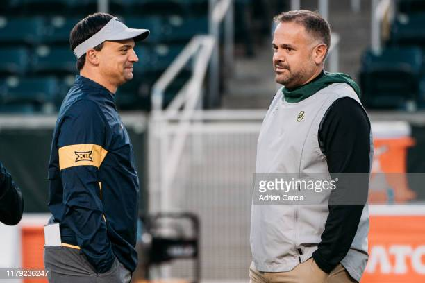 Head coaches Matt Rhule of the Baylor Bears and Neal Brown of the West Virginia Mountaineers talk in the middle of the field during warm ups at...