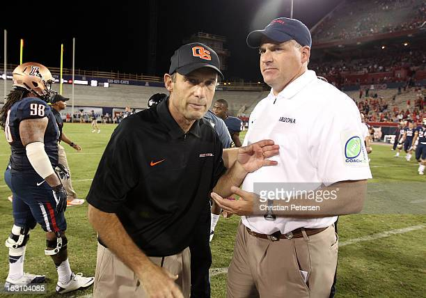 Head coaches Mike Riley of the Oregon State Beavers and Rich Rodriguez of the Arizona Wildcats come together following the college football game at...