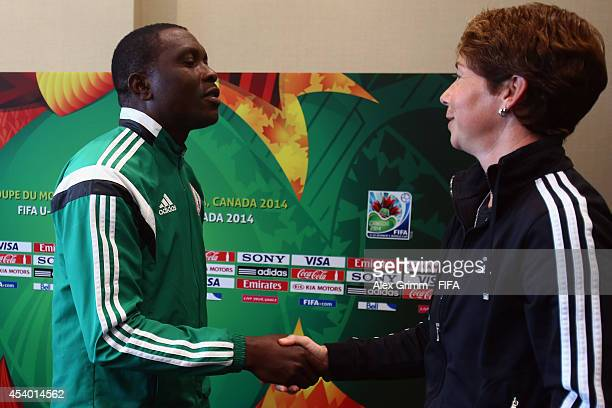 Head coaches Peter Dedevbo of Nigeria and Maren Meinert of Germany shake hands after the FIFA Women's World Cup Canada 2014 Press Conference at Le...