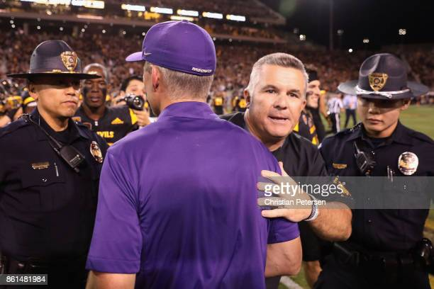 Head coaches Todd Graham of the Arizona State Sun Devils and Chris Peterson of the Washington Huskies shake hands following the college football game...