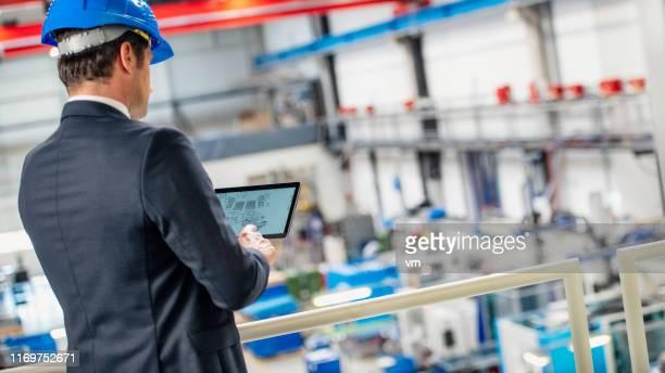 工場の生産プロセスを制御するためにデジタルタブレットを使用するヘッドエンジニア - 見渡す ストックフォトと画像