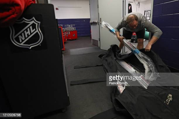 Head Equipment Manager Paul Boyer of the Detroit Red Wings packs a stick bag after the Detroit Red Wings against the Washington Capitals game was...