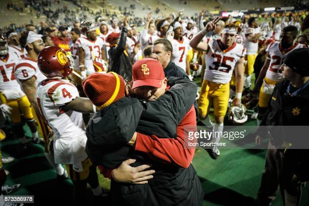 USC head football coach Clay Helton gets a hug from a fan after the Colorado Buffalos game versus the USC Trojans on November 11 at Folsom Field in...