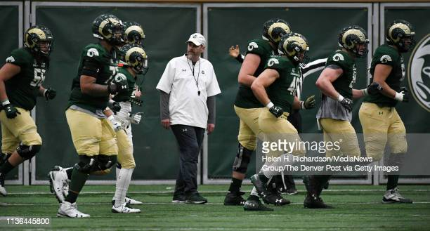 CSU head football coach Mike Bobo center watches his players as they take the field during the team's 2019 Rams football spring game at the team's...