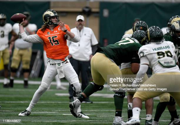 CSU head football coach Mike Bobo in the background watches as quarterback Collin Hill #15 gets ready to make a pass during the team's 2019 Rams...