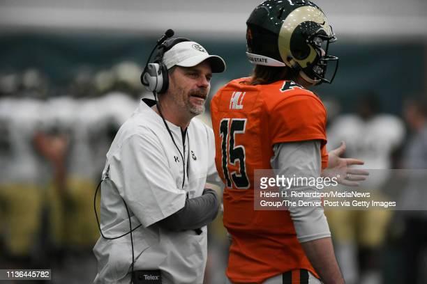 CSU head football coach Mike Bobo left talks with CSU Rams quarterback Collin Hill #15 during the team's 2019 Rams football spring game at the team's...