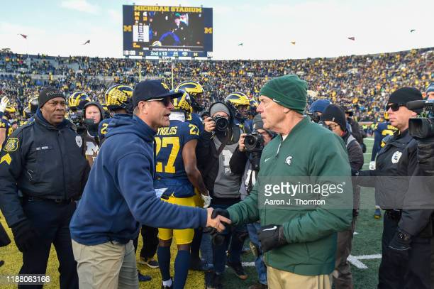 Head Football Coaches Jim Harbaugh of the Michigan Wolverines and Mark Dantonio of the Michigan State Spartans shake hands after a college football...