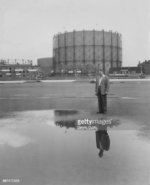 Head groundsman Bert Lock and the landmark gasometer are reflected in a pool of water on the wicket of the cricket pitch as bad weather and rain...