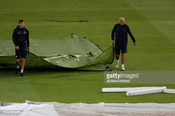 Head Groundsman Mick Hunt , who is set to retire at the end of the 2018 season, helps to pull the covers on during a rain delay on the second day of...