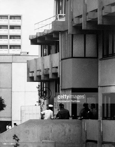 A head leaning out of the window of an Olympic Village's building observed by journalists and curious people on the courtyard outside he's a member...