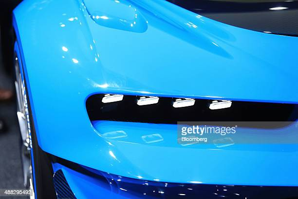 Head lights sit illuminated on a luxury Bugatti Vision Gran Turismo sports automobile produced by Volkswagen AG during previews to IAA Frankfurt...