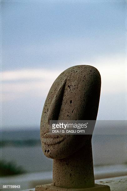 Head of a Cycladic idol on the background of the coast Cyclades islands Greece Cycladic civilisation