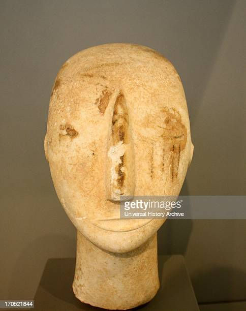 Head of a Cycladic statue Sculptured nose mouth and ears Painted eyes and red vertical striations on the right cheek Parian marble found on Amorgos...