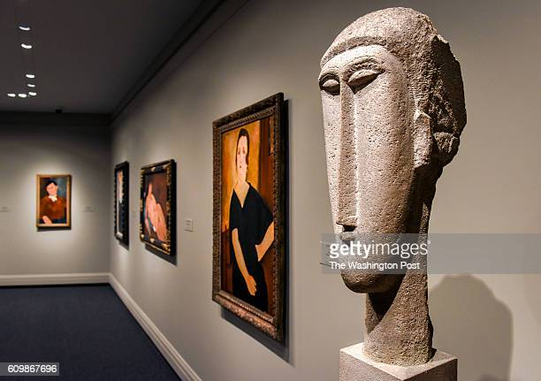 Head of a Woman right by Amadeo Modigliani along with some of his paintings in one of the new galleries during a look at the east wing of the...