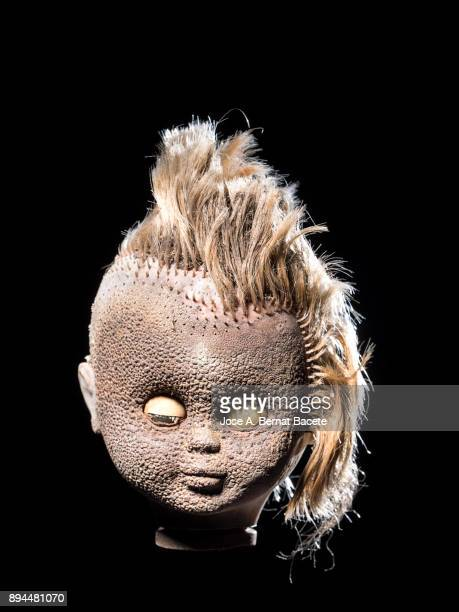 head of an old wrist broken with blond hair, torn and degraded by the fire, on a black background. spain - dead female bodies stockfoto's en -beelden