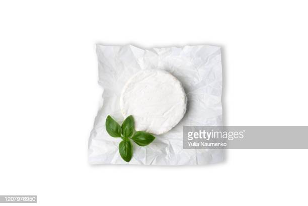 head of camembert or brie cheese with a sprig of green basil. isolated on white background. - brie stockfoto's en -beelden