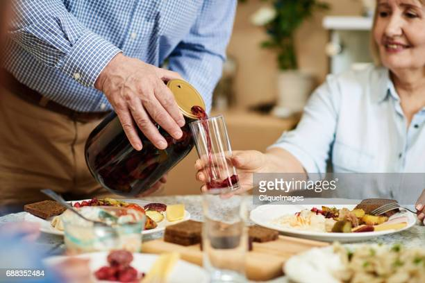 head of family pouring out kompot - cliqueimages - fotografias e filmes do acervo