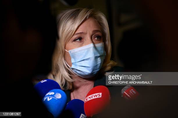 Head of far-right party Rassemblement National Marine Le Pen answers the press as she leaves after a hearing in her trial for tweeting images of the...