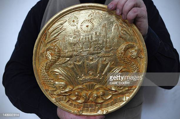 Head of Historic Carving Alan Lamb poses holding a 'Thames Pageant Roundel' that will decorate the Royal Barge in which Britain's Queen Elizabeth II...