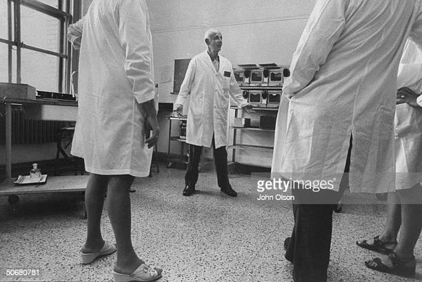 Head of Institute of Exprimmental Research and Surgery Dr Hans Selye talking to unidentified people in a laboratory during an experiment