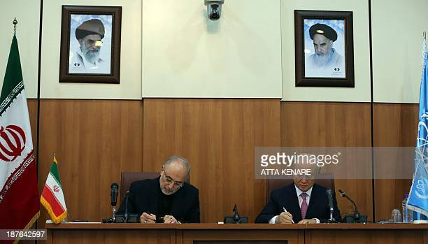 Head of Iran's Atomic Energy Organisation Ali Akbar Salehi and International Atomic Energy Agency Director General Yukiya Amano sign a protocol under...
