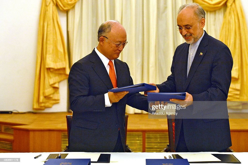 Head of Iran's Atomic Energy Organization Ali Akbar Salehi (R) and Director General of the International Atomic Energy Agency (IAEA) Yukiya Amano exchange folder after the Iran nuclear talk meetings concluded with a deal in Vienna, Austria on July 14, 2015.
