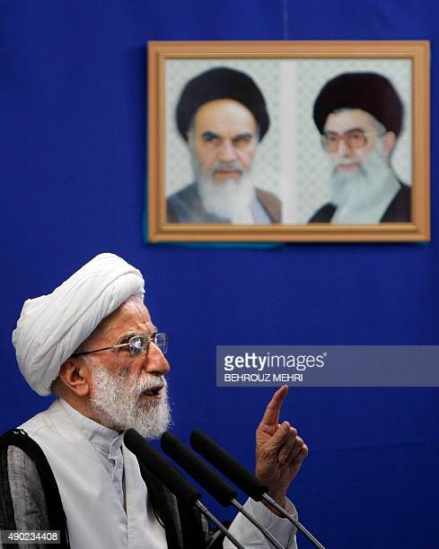 Head of Iran's electoral body the Guardians Council Ahmad Jannati speaks under the portraits of Iran's late founder of Islamic republic Ayatollah...