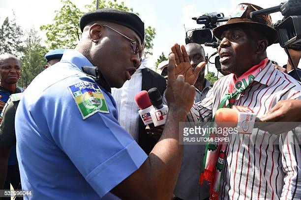 Head of Lagos police command Fatai Owosenii speaks to workers and civil society groups during a protest demanding that the government reinstate...