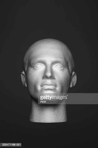 Head of mannequin against black background, close-up