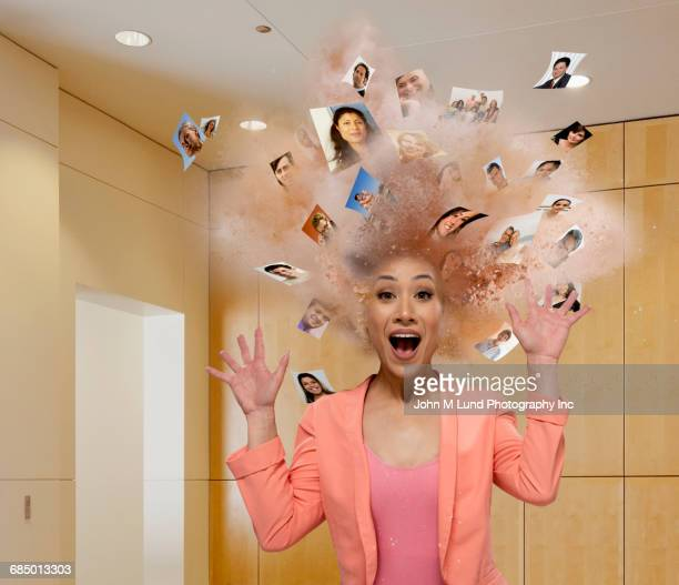 Head of Mixed Race businesswoman exploding with faces of people