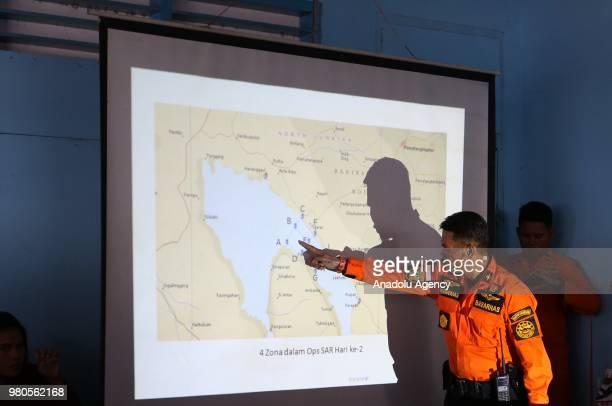 Head of North Sumatra National SAR Agency Budiawan shows the sinking location of KM Sinar Bangun on a map in Lake Toba Simalungun North Sumatra on...