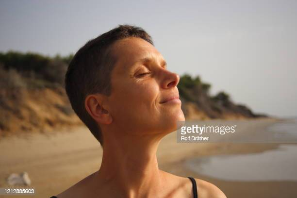 head of one woman with short hair smiling and enjoying the sun with closed eyes at the beach - mid adult women stock pictures, royalty-free photos & images