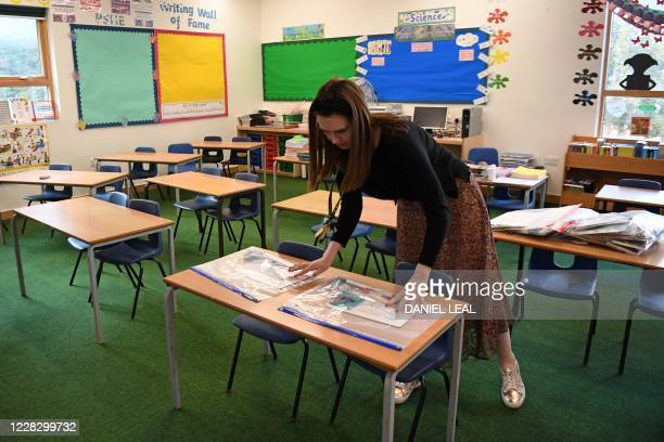Head of School, Cristina King demonstrates how children's belongings will be kept sealed in plastic as the school is prepared to provide a teaching...