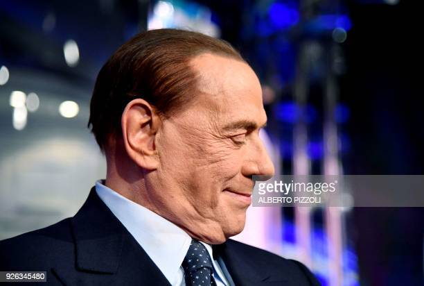 TOPSHOT Head of the centreright Forza Italia Silvio Berlusconi poses on March 2 2018 on the set of the broadcast Porta a Porta a programme of Italian...