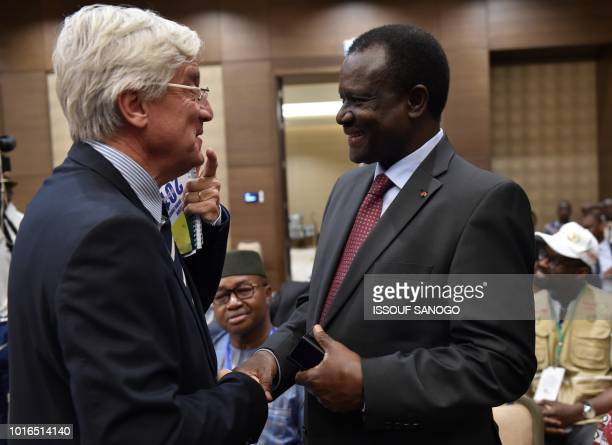 Head of the European Union Delegation to Mali Alain Holleville shakes hands with head of the Economic Community of West African States election...