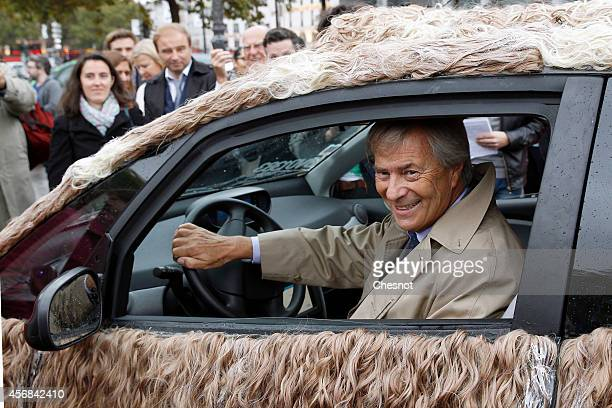 Head of the French industrial group Bollore Vincent Bollore poses sitting one of the nine new customized Autolib cars on October 8 2014 in Paris...