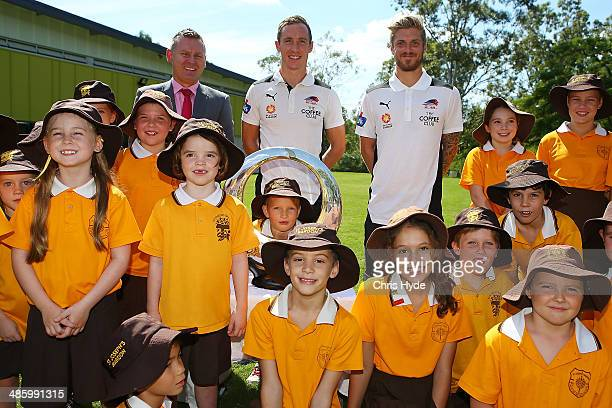 Head of the Hyundai ALeague Damien de Bohu and Matthew Smith and Luke Brattan of the Roar pose with the ALeague Championship trophy and students from...