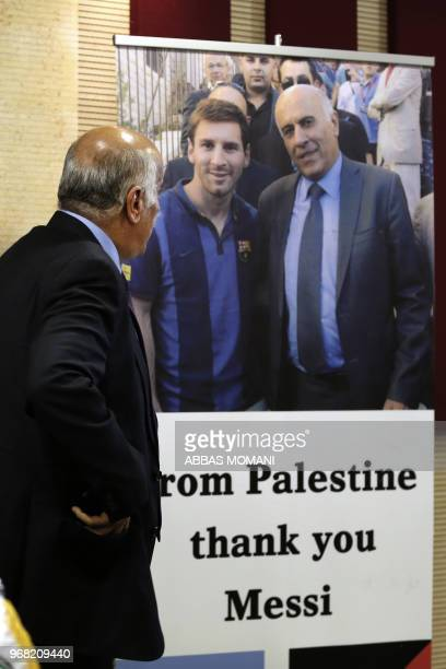 Head of the Palestinian Football Association Jibril Rajoub stands in front of a sign addressed to Argentina's star player Lionel Messi during a press...