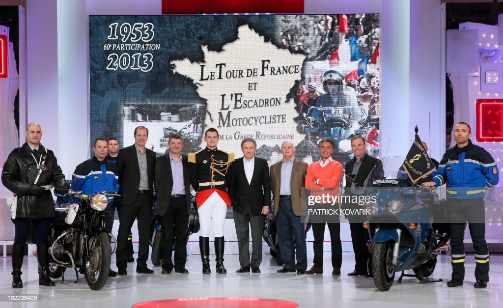 Head of the Tour de France cycling race Christian Prudhomme (4thL) former Tour de France winner Bernard Thevenet (5thL), TV host Michel Drucker (C), journalists Jean-Paul Ollivier (4thR) and Gerard Holtz (3rdR) and former Tour de France winner Bernard Hinault (2ndR) pose with pilots of motocyclists squadron of the Republican guard, on February 20, 2013 in Paris, as part of the celebrations of the squadron's 60th anniversary.