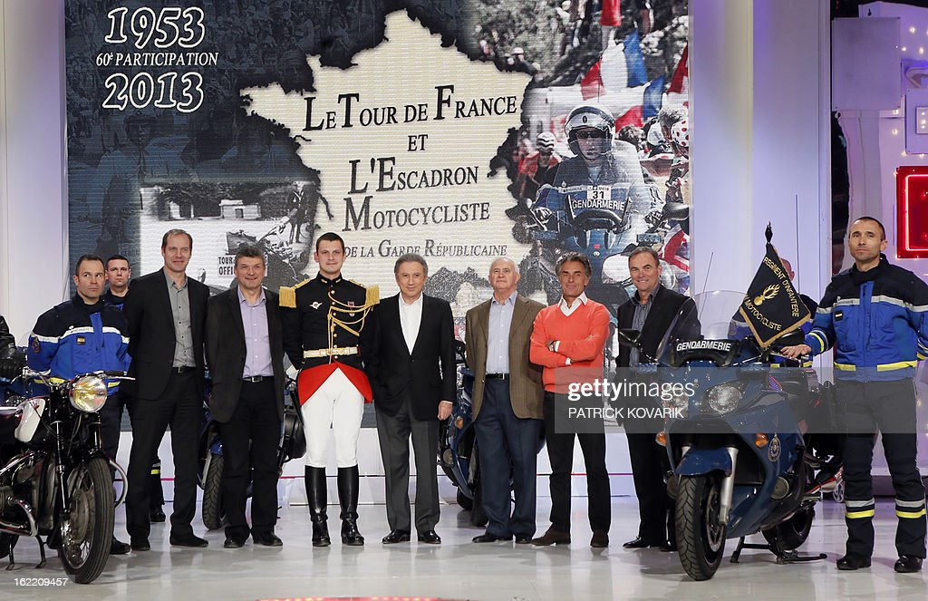 Head of the Tour de France cycling race Christian Prudhomme (3rdL) former Tour de France winner Bernard Thevenet (4thL), TV host Michel Drucker (C), journalists Jean-Paul Ollivier (4thR) and Gerard Holtz (3rdR) and former Tour de France winner Bernard Hinault (2ndR) pose with pilots of motocyclists squadron of the Republican guard, on February 20, 2013 in Paris, as part of the celebrations of the squadron's 60th anniversary.