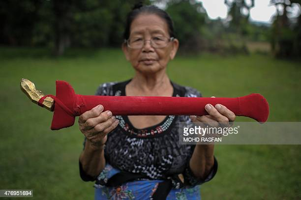 Head shaman from the KadazanDusun tribe Singkaban Kowil holds a dagger called hulu karis at her residence in Damat a village in the district of...