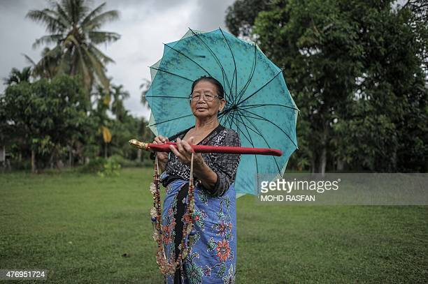 Head shaman from the KadazanDusun tribe Singkaban Kowil holds a dagger called hulu karis and an amulet called kamagi at her residence in Damat a...