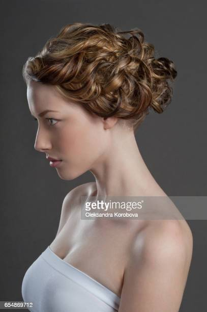 Head shot in profile on a neutral, seamless background of a beautiful young woman
