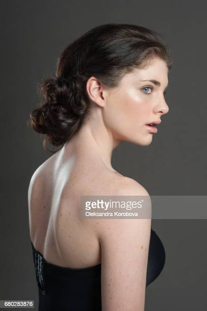 head shot in profile on a neutral, seamless background of a beautiful young woman - istock photo stock pictures, royalty-free photos & images