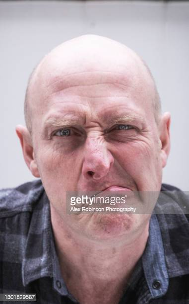head shot of a bald man in his fifties pulling a confused, ugly face - ugly bald man stock pictures, royalty-free photos & images